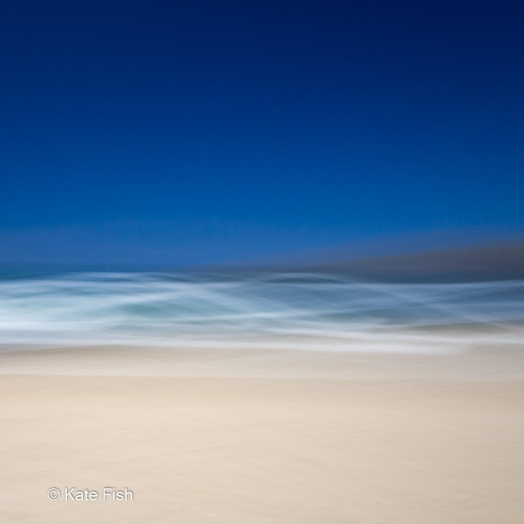 Bewußte Kamerabewegung (ICM)ICM Beach Art mit Wellenlinien aus den Schaumkronen der Wellen und beigem Sandstrand und tiefblauem Himmel, kreativ verwischt durch ziehen der Kamera während der Aufnahme