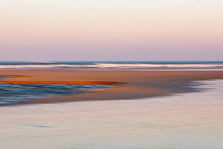 ICM Technik als Technik kreativ mit der Kamera zu sein, am Strand, durch einfaches Ziehen der Kamera verschwimmen hier die Konturen des Baches, des Sandstandes und der Wellen zu einem abstracten Bild mit geschwungenen Linienaus blau, orange und fast silber-rosa. Letzteres durch das Rosa am frühen Morgenhimmel über dem Strand von Mawgan Port in Cornwall