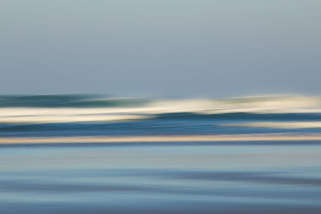 Kreativ mit der Kamera-BeachArt genannte Technik der horizontalen Kamerabewegung am Strand. Hier ist ein blaue verwischte Wellen, weiße verwischte Wellenschaumkronen und ein blaugrauer Morgenhimmel als Streifenbild mit Textur .