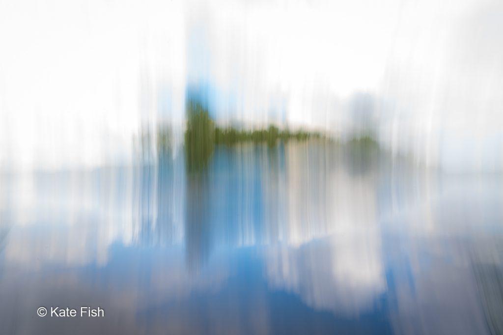 Bewusste Kamerabewegung ICM einer grünen Insel in einem See mit Spiegelung bei vertikaler Bewegung der Kamera