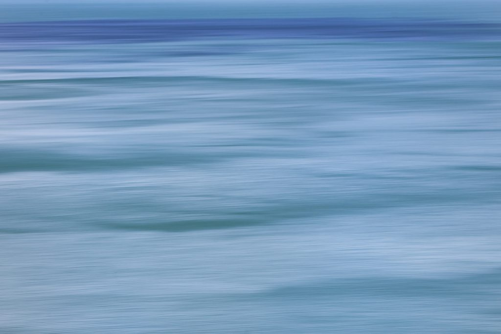 Several shades of blue horizontal lines that look like drawn - created using the ICM technique of panning horizontally
