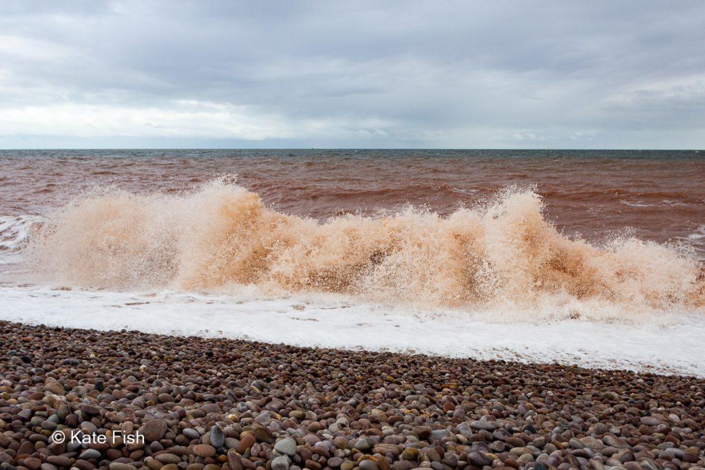 Spritzende Wellen am Strand, direkt vor der Kamera, da das in Wellenfotos dramatischer wirkt