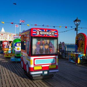 Englischer Spielzeugbus in dessen Fenster es regnet, für Kinder auf dem Pier in Paignton in quietschrot und mit englischer Flagge. Das ist englischer Humor und englische Kultur.