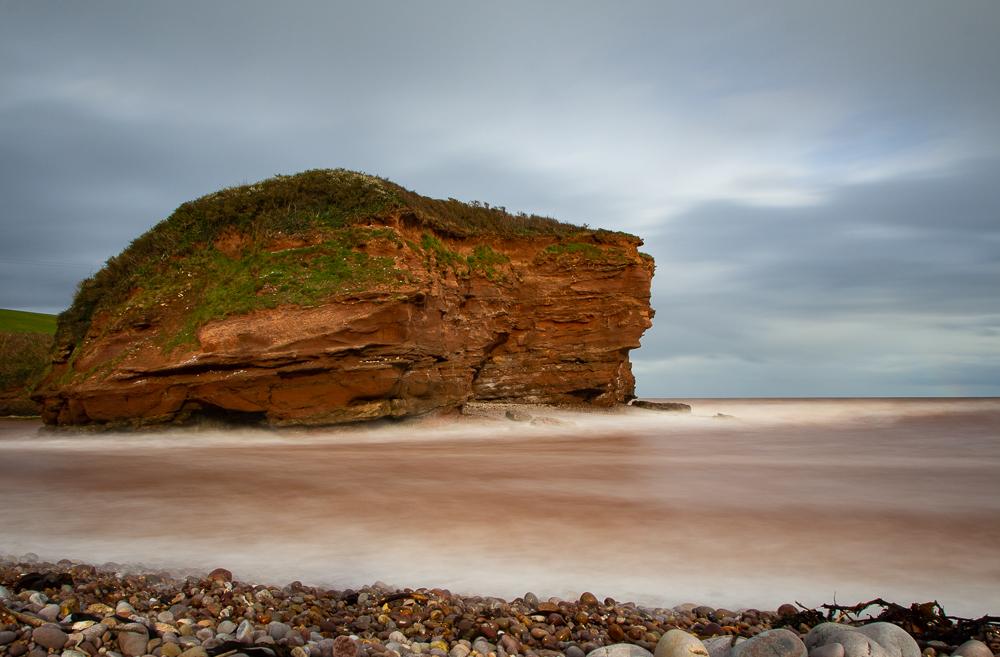 Budleigh Salterton roter Fels im Meer mit fluffigen Wellen durch Einsatz eines Graufilters