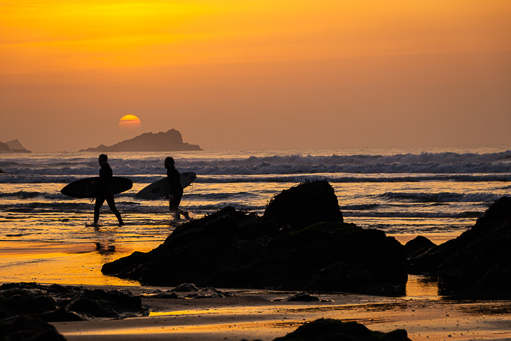 Newquay Fistral beach mit Surfern als Silhouette vor einem atemberaubenden Sonnenuntergang als Beispiel für ein Foto auf der Fotowanderreise Cornwall