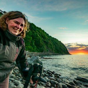 Kate Fish fotografierend bei Sonnenuntergang an der SüdWestküste Englandsküste