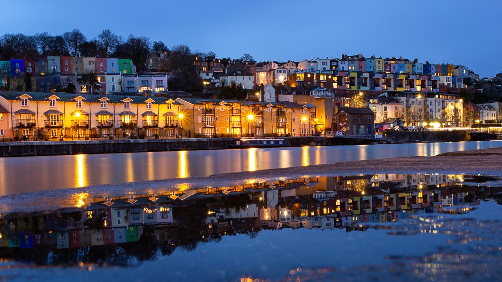 Blaue Stunde in Bristol am Hafen mit den bunten Häusern von Hotwells und den Lichtern, die sich im Wasser spiegeln. Langzeitbelichtung