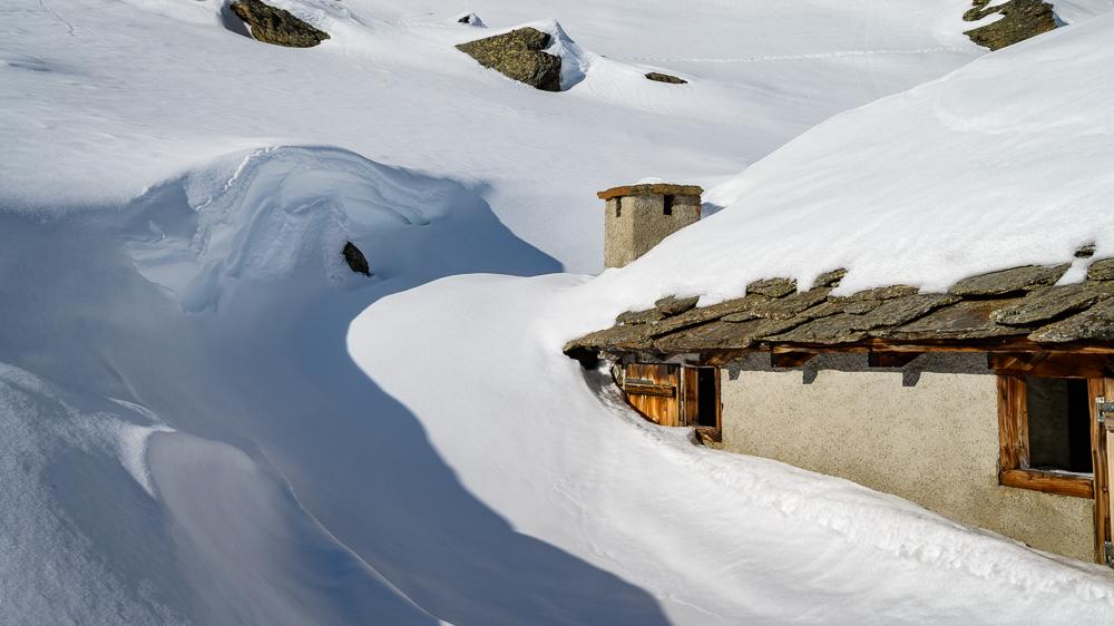 Völlig bis über die Fenster eingeschneiter Stall am Berg als Motiv beim Winterlandschaft fotografieren. Schöner weißer Schnee und Schatten, die die Schneewehe hervorheben.