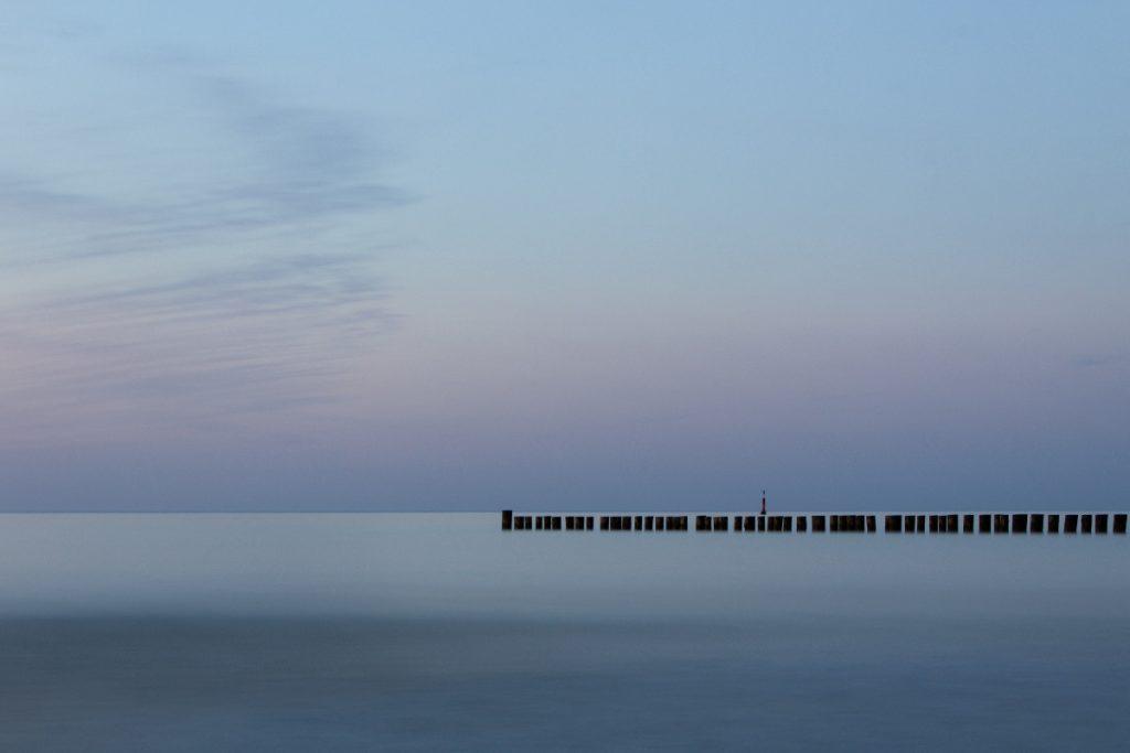 Blaue Stunde Zingst an der Ostsee, Blich über die Stille Ostsee mit Buhnen im Vordergrund in ein mystisches blau-lila getaucht