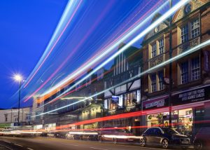 Blue hour picture of Gloucester Road in Bristol with bus light tracks and street light stars; Blaue Stunde Bristol Gloucester Road mit Buspuren und Blendenstern in der Strassenbeleuchtung