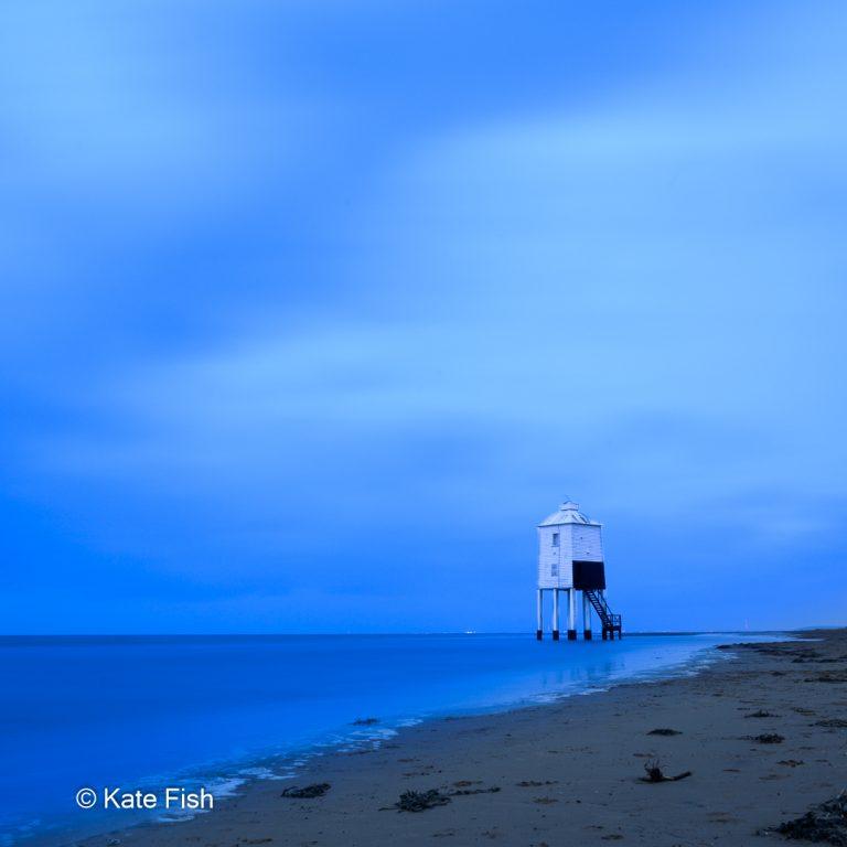 Blaue Stunde am Strand in Burnham-on-Sea mit dem weißen Lower Lighthouse als Kontrast zu den intensiven Blautönen von Meer und Himmel. Langzeitbelichtung Wolken verwischt