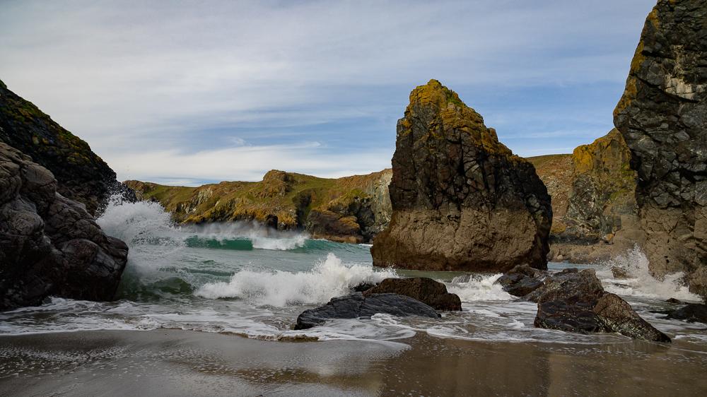 Kynance Cove an der Küste des Lizard Cornwall in der Bucht bei schönem Wetter mit Strand, Wellen und Felsen im Wasser