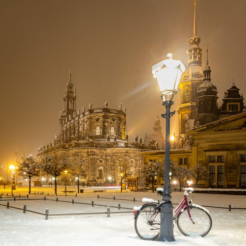 Dresden Stadtkirche im Schnee und goldenem Glanz der nächtlichen Beleuchtung im Schneetreiben mit Fahrrad an leuchtender Straßenlaterne im Vordergrund als Beispiel im Fotografie Kurs - schöne Winterbilder vor der Haustür