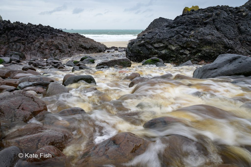 Kynance Cove Wasserlauf über bunte Serpentinesteine inin Langzeitbelichtung