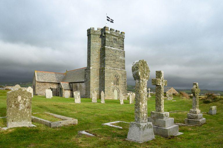 Tintagel Kirche mit Friedhof mit keltischen Kreuzen im Abendlicht und kornischer Flagge als Beispiel für ein Fotomotiv auf der Fotowanderreise Cornwalls Nordenit