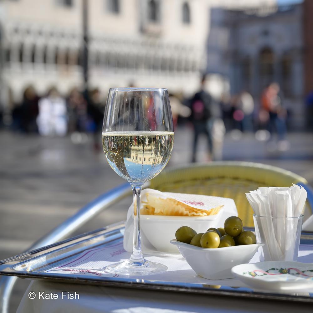 Spiegelung des Markus Doms im Sektglas auf einem Gedeck aus Oliven, Chips und Prosecco auf silbernem Tablet auf einem Tisch auf dem Markusplatz in Venedig als Beispiel, wie du kreativ mit der Kamera sein kannst