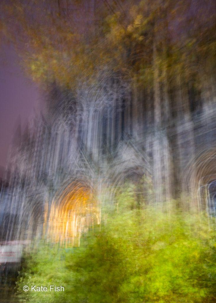 Bewusste Kamerabewegung in Form eines Vierecks in der Luft zur Vervielfältigung der Linien eines Gebäudes in Bristol mit beleichtetem Eingang und Aussehen wie eine Kirche. Aufgenommen zum besonderen Licht der blauen Stunde