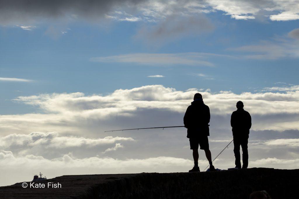 Silhouette zweier Angler im Morgenlicht als Beispiel für Neugier erzeugen mit Silhouetten