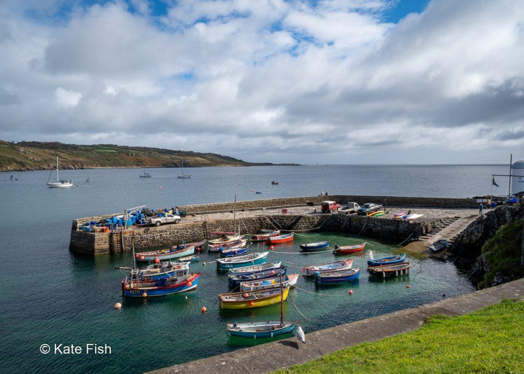 Coverack Hafen auf der Lizard Halbinsel in Cornwall mit kleinen Fischerbooten und einer Kaimauer, die den Hafen wie ein U umschließt. Türkisblaues Wasser, klar bis auf den Grund und im Hintergrund die Küste