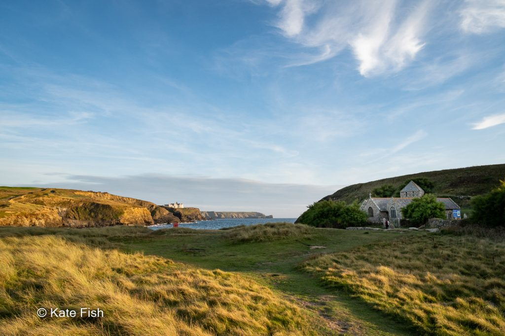 Die kleine Kirche in der Gunwalloe Church Cove auf der Lizard Halbinsel in Cornwall von der Düne aus mit dem Weitwinkel so fotografiert, dass das Meer und die Kirche zu sehen sind. Sie Abendsonne beleuchtet die Steilküste auf der linken Seite und obwohl die Kirche im Schatten der sie schützenden Steilküste liegt, ist sie deutlich zu sehen.