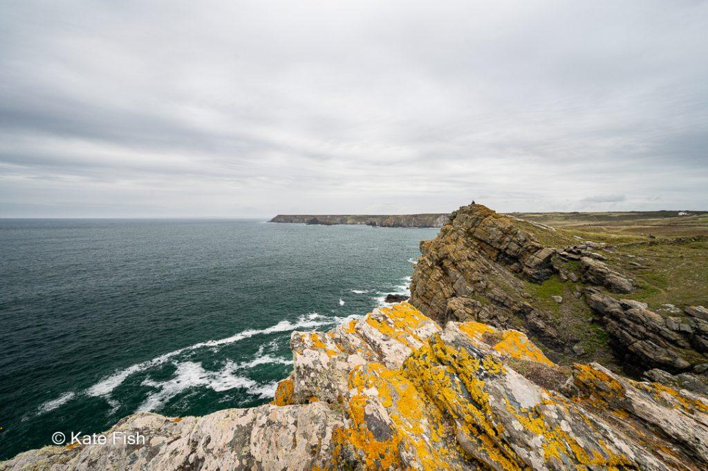 Winziger Mensch auf Klippe an der Küste in Cornwall im Mittelgrund mit flechtenbewachsener Steilküste als Vordergrund und Bucht als Hintergrundals Größenvergleich für Tiefe in Landschaftsfotos