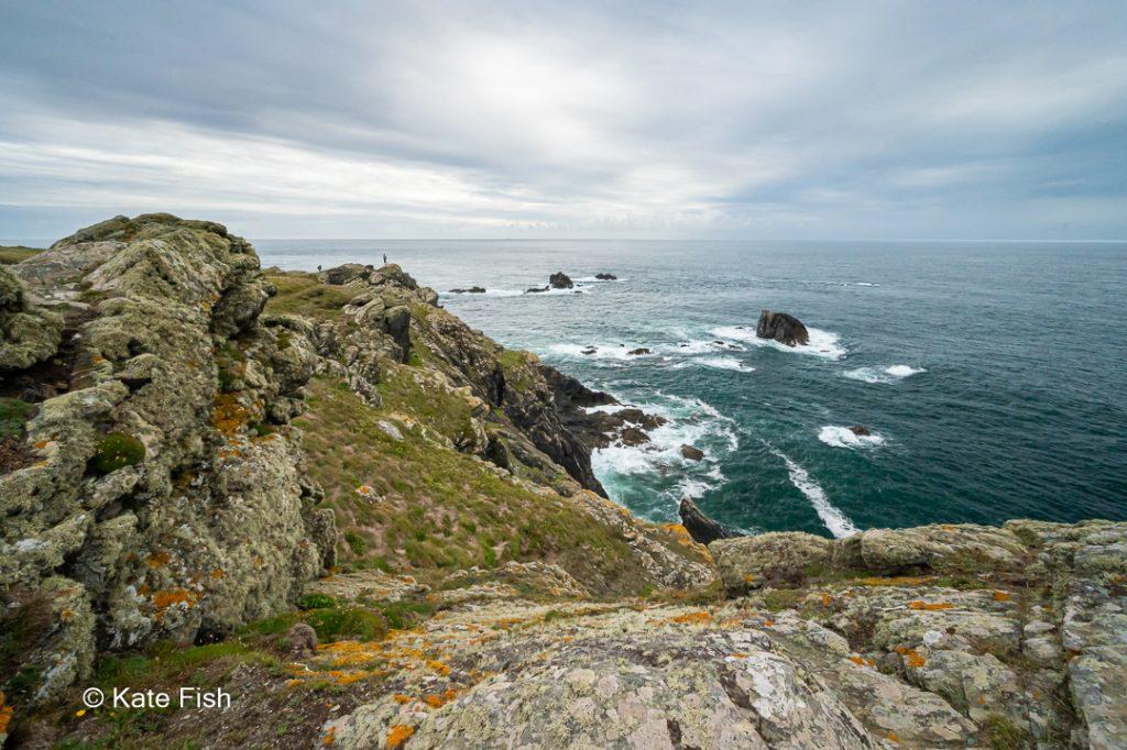 Rauhe Felsküste mit orangenen und grünen Flechten auf den Felsen am Lizard Point auf der Lizard Halbinsel in Cornwall mit winzigen Menschen im Bild, die die Höhe der Küste eindrucksvoll demonstrieren. Trotz graublauem Himmel ist das Wasser dunkeltürkis