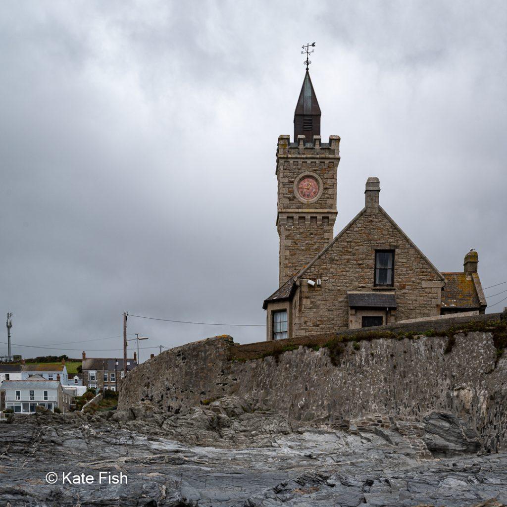 Bickford-Smith Institute mit Uhrenturm in Porthleven auf der Lizard Halbinsel in Cornwall vom Strand aus fotografiert bei stürmischem Wetter mit grauem Wolkenhimmel