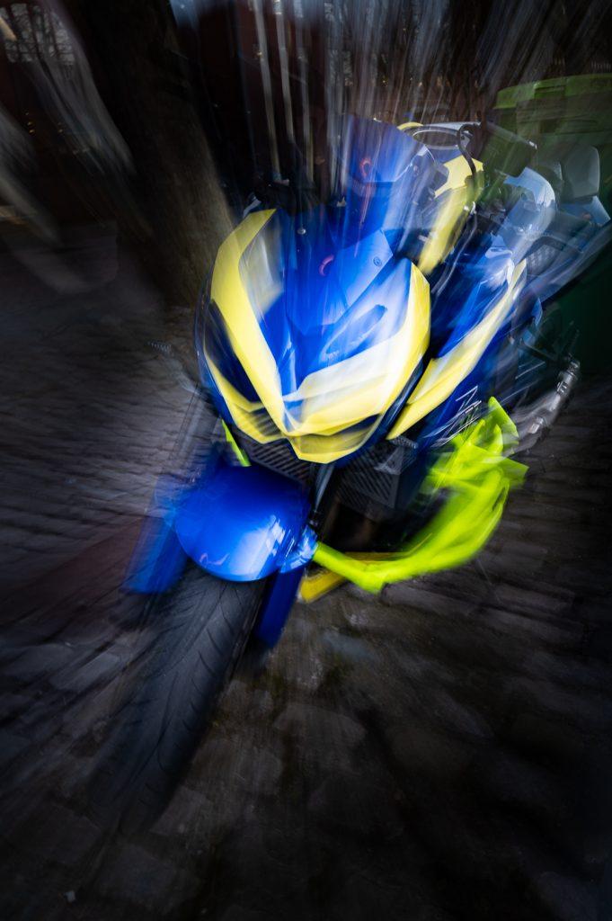 Bewusst bewegte Kamera in form von zoom burst ICM eines blau gelben Motorrads, das dadurch erscheint als würde es fliegen.