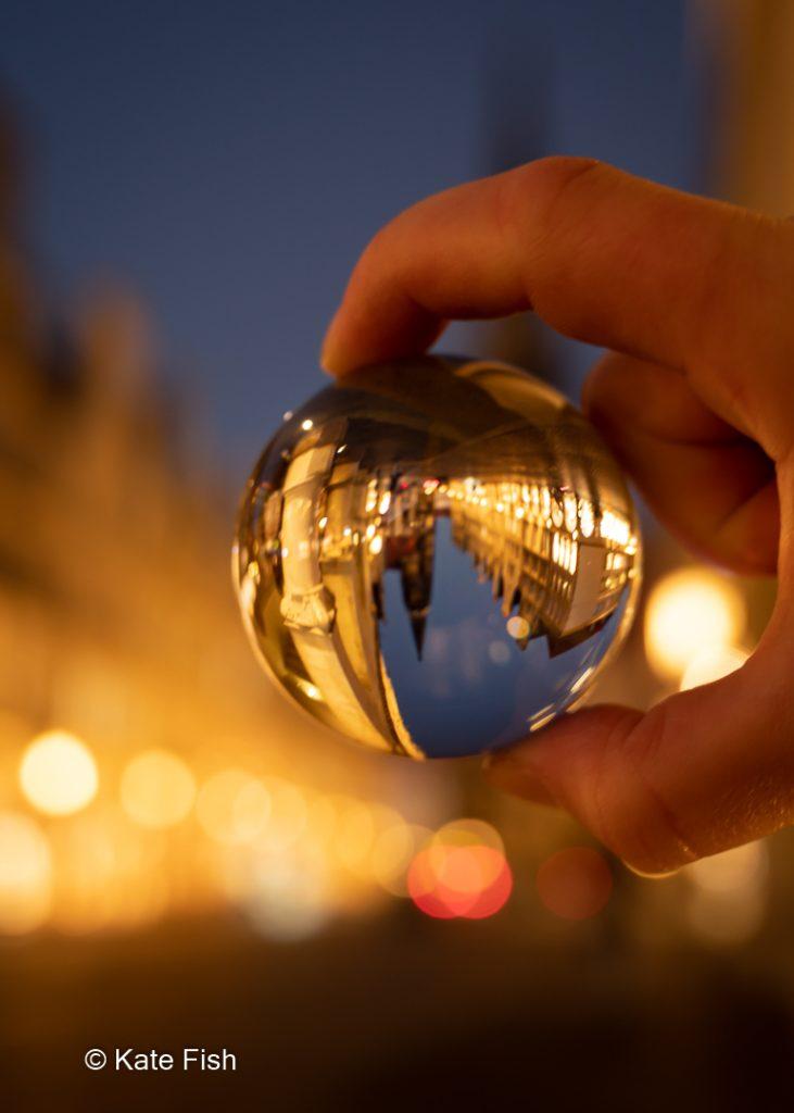 Glaskugel in der Hand gehalten zur blauen Stunde in Münster mit der Lambertikirche auf dem Kopf als Beispiel für Spiegelungen in Glas