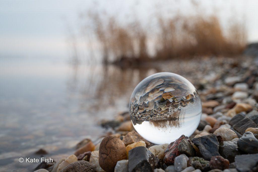 Spiegelung in einer Glaskugel am See mit Kieselsteinen, Schilf und Himmel als Beispiel für Spiegelungen in Glas
