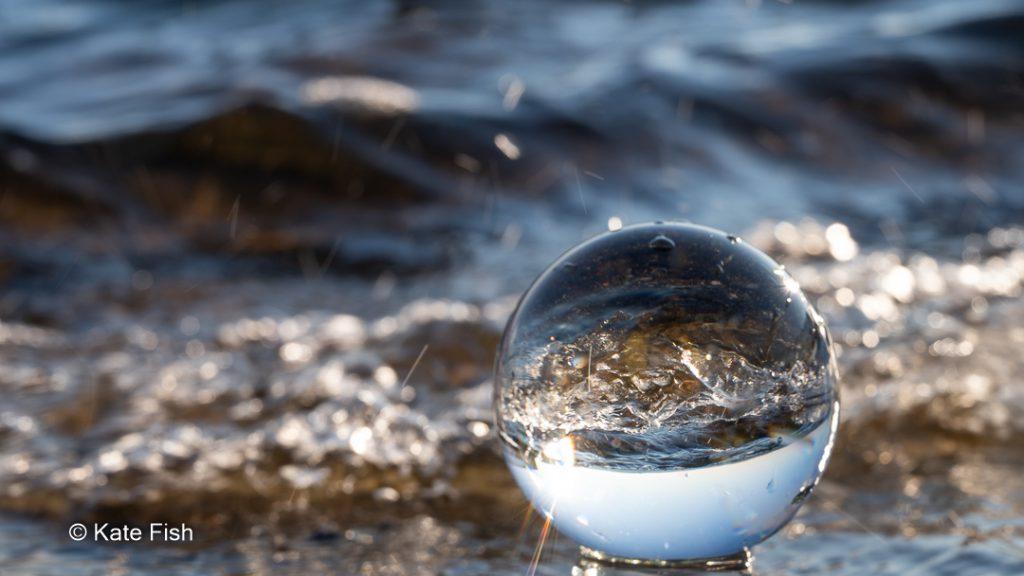 Welle gespiegelt in einer im Wasser liegenden Glaskugel als Beispiel für Spiegelungen in Glas