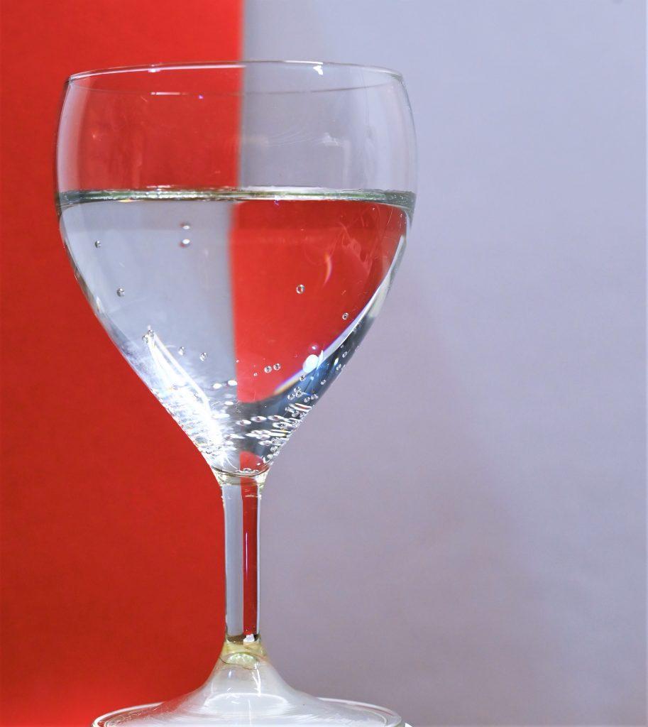 Spiegelung in Glas durch einen roten Karton bis zur Mitte hinter einem mit Wasser gefüllten Weinglas