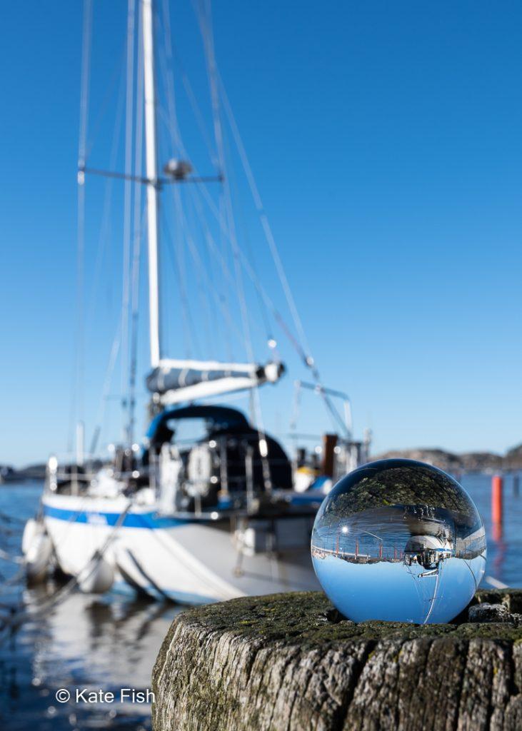 Glaskugel auf Buhne mit Jacht im Hintergrund, die sich in der Glaskugel spiegelt. Strahlend blauer Himmel
