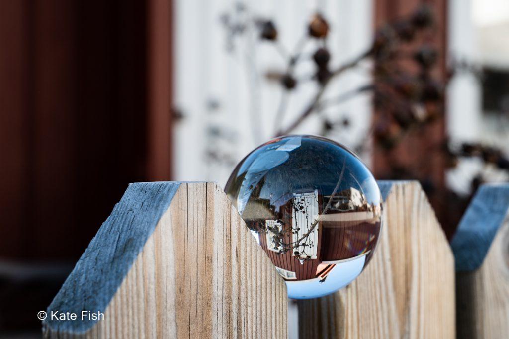 Glaskugel eingeklemmt in zwei helle Zaunpfähle, die dann in der gleichen Schärfenebene liegen und somit noch scharf sind. Hier mit unscharfem Haus im Hintergrund