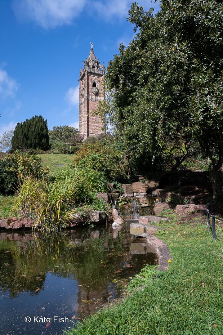Blick vom Teich auf den Cabot Tower im grünen Brandon Hill in Bristol. Ohne einen Polfilter wurde die Spiegelung auf dem Wasser nicht entfernt, so dass es keinen schönen Kontrast zu dem hellen viereckigen Turm bietet., sondern das Bild durch die Spiegelung des Turmes und der Wolken im Wasser recht unruhig macht.