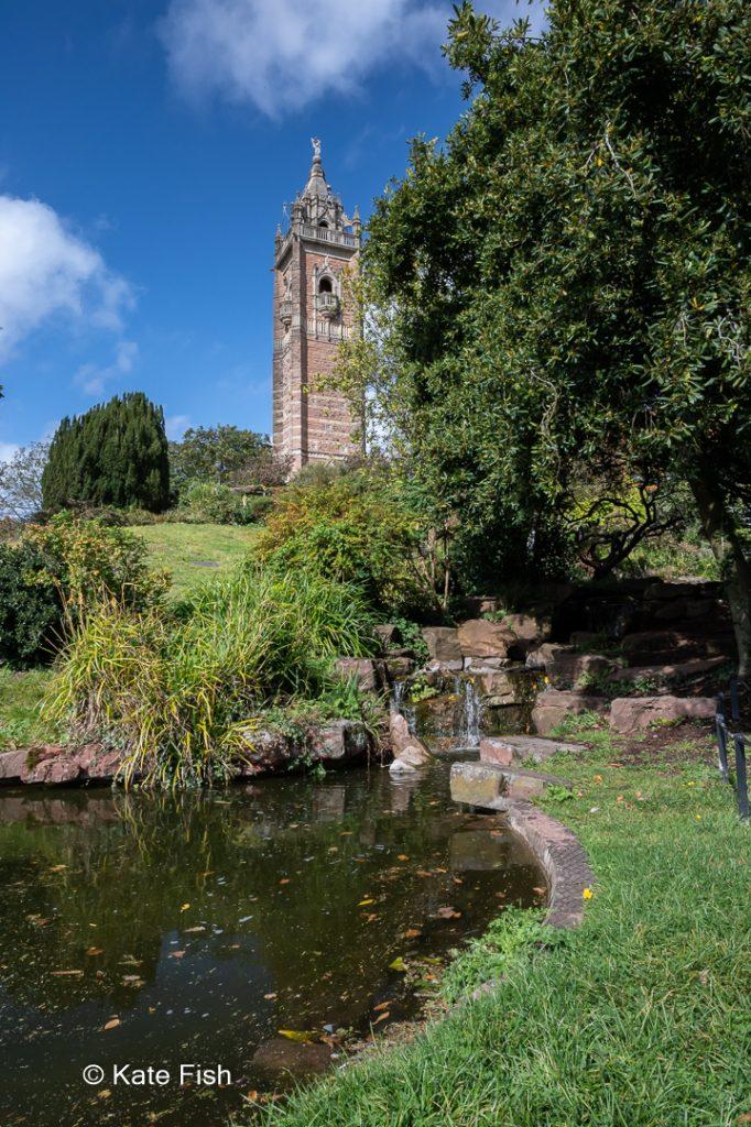 Blick vom Teich auf den Cabot Tower im grünen Brandon Hill Park in Bristol. Mit einem Polfilter wurde die Spiegelung auf dem Wasser entfernt, so dass es einen schönen dunklen Kontrast zu dem hellen viereckigen Turm bietet.