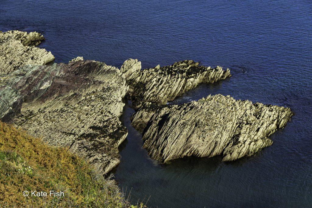 Der Einsatz eines Polfinters in der Landschaftsfotografie macht hier das Wasser tiefblau, indem der Filter die Spiegelung an der Oberfläche wegnimmt. Von der Steilküste auf einen bizarren Fels herunter fotografiert in Cornwall