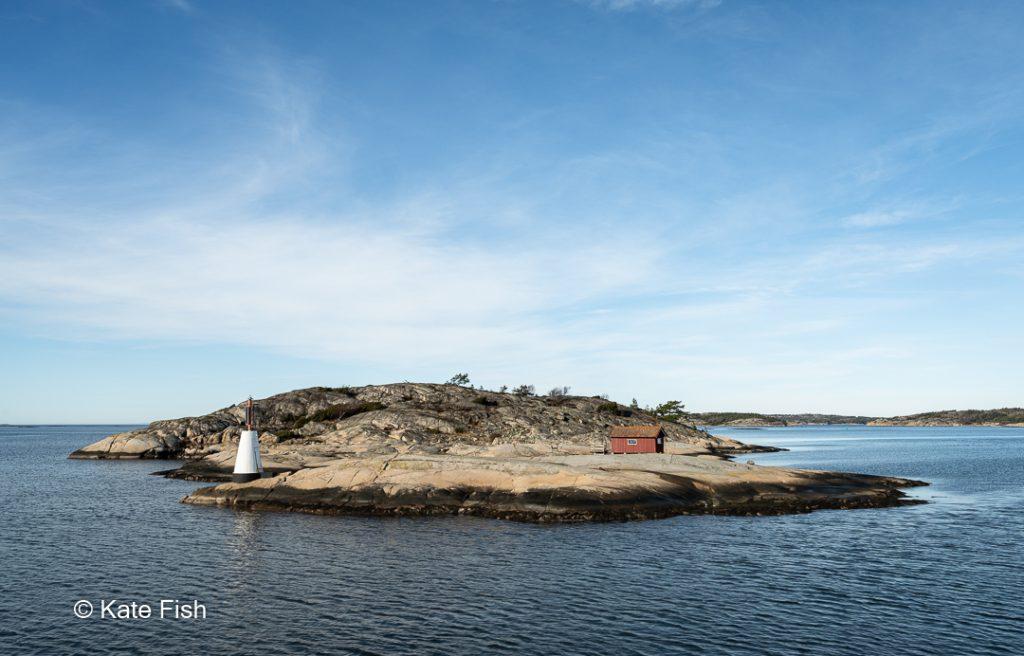 Kleine Westschäreninsel mit Leuchtturm und Holzhaus auf der Bootsstrecke zu den Koster Inseln als Beispiel für schöne Fotolocations in Schweden