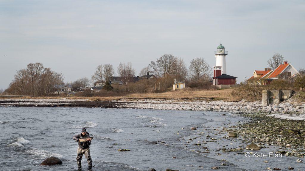 Leuchtturm von Smygehuk vom Hafen aus fotografiert mit Meer und erfolgreichem Angler im Vordergrund