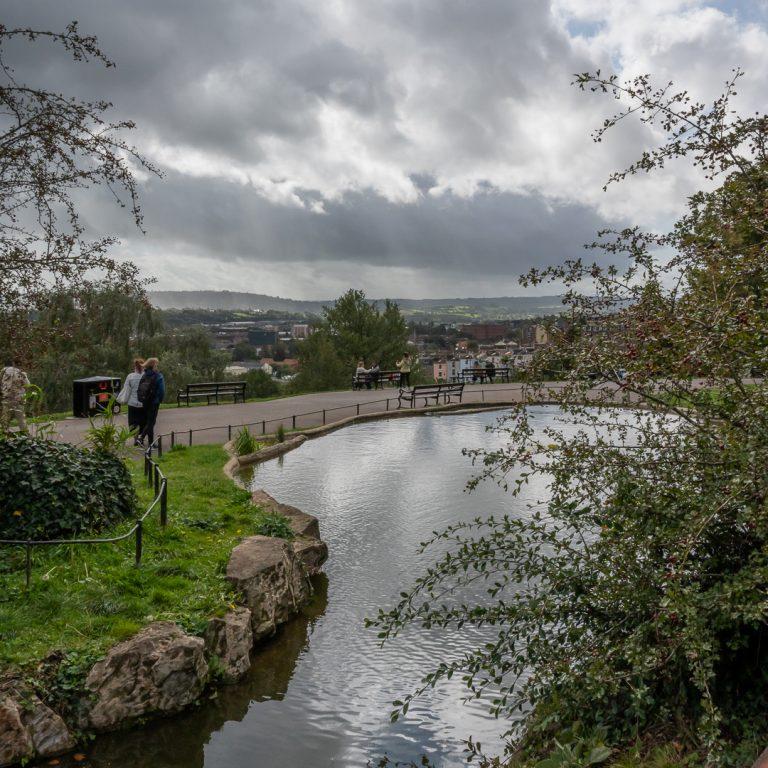Teich vor dem Cabot Tower auf dem Brandon Hill im gleißenden Gegenlicht und mit starker Spiegelung der hellen Wolkendecke auf der Wasseroberfläche, da kein Polfilter verwendet wurde.