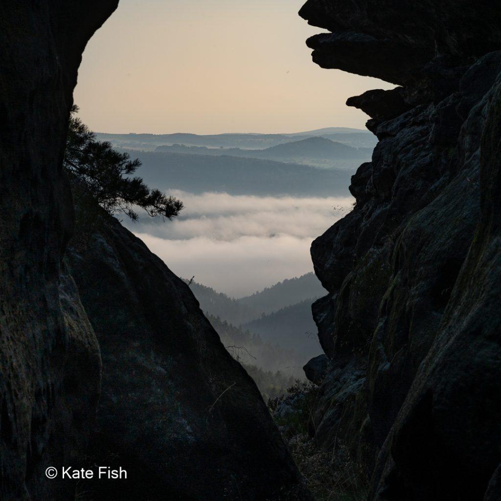 Silhouette als Vordergrund mit Nebel und Dunstiger Landschaft durch die Felsspalte fotografiert.