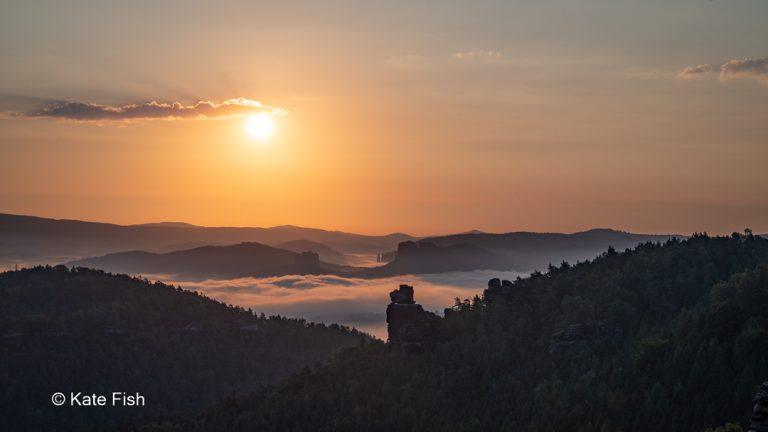 Sonnenaufgang auf dem Gohrisch mit Blick nach Osten zum Papststein und Nebel über der Elbe