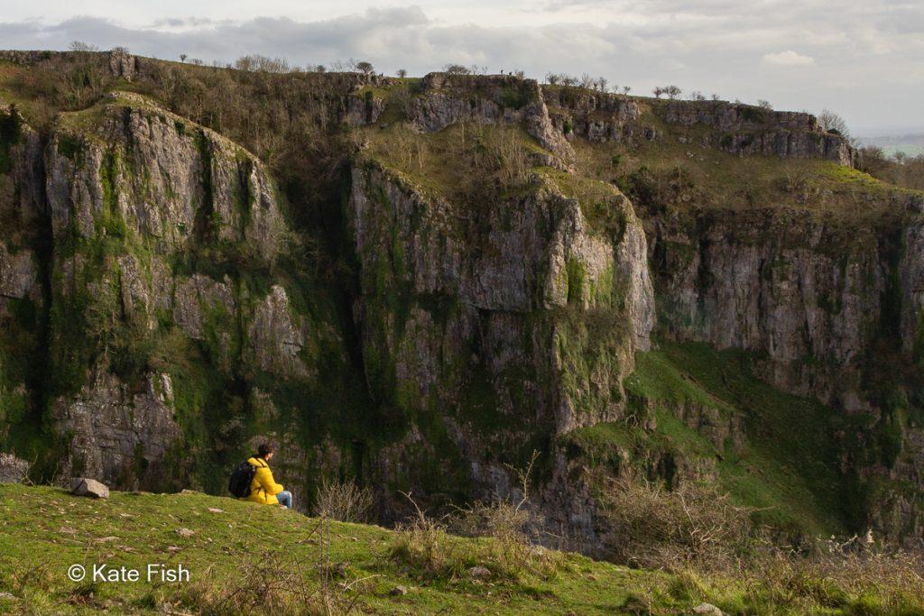 Winziger Mensch in gelber Jacke im Bild vor Cheddar Gorge Felsen als Größenvergleich für Tiefe in Landschaftsfotos