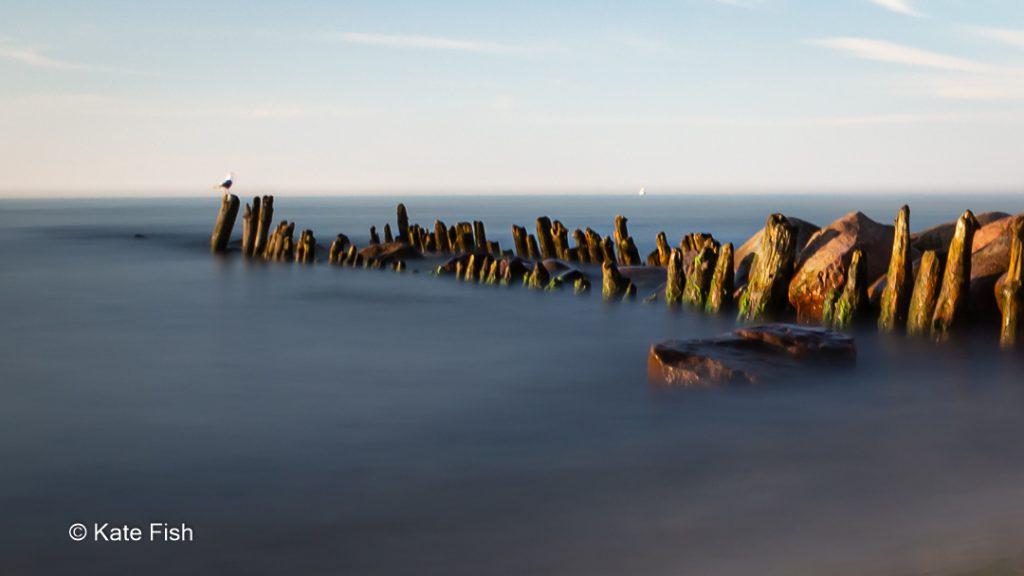 Langzeitbelichtung Wolken und Wasser sind verwischt Heiligen Damm Ostsee mit Buhnen und Möwe drauf zur goldenen Stunde
