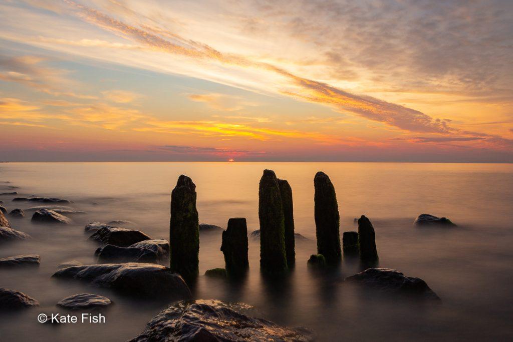 Langzeitbelichtung Wolken kaum verwischt trotz 25s Belichtungszeit, Sonnenuntergang an der Ostsee zur goldenen Stunde mit Buhnen und Steinen im durch die Langzeitbelichtung glatten WasserWasser
