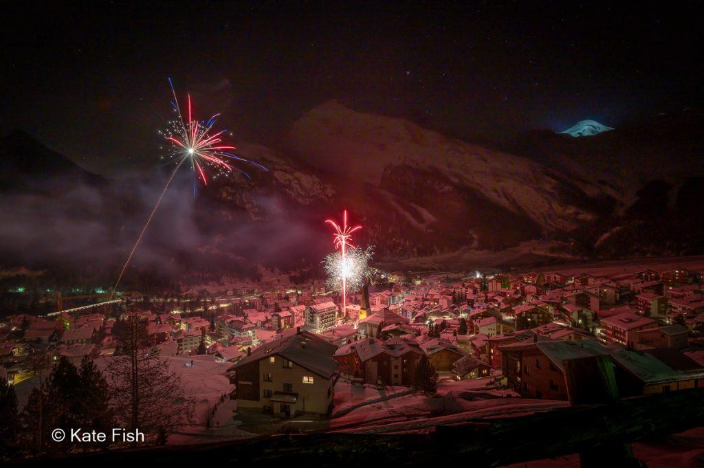 Selektive Tiefe in Landschaftsfotos, hier Silvesterfeuerwerk in Saas-Fee mit scharfem Feuerwerk und Dorf und unscharfem Zaun als Vordergrund und unscharfen Bergen als Hintergrund. Alles in einem Rosa Licht drch das Feuerwerk und den Schnee, der es reflektiert.