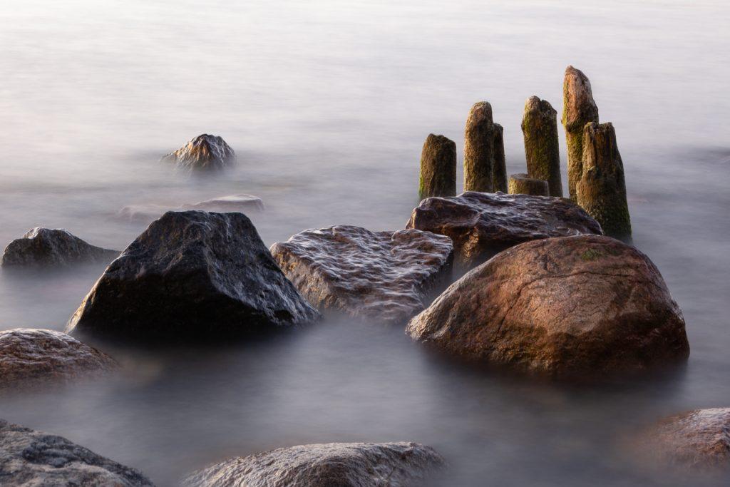 Buhnen im Abendlicht, umspült von waberndem Wasser durch Langzeitbelichtung als Beispiel für Wellenfotos, in denen gar keine Welle mehr zu erkennen ist