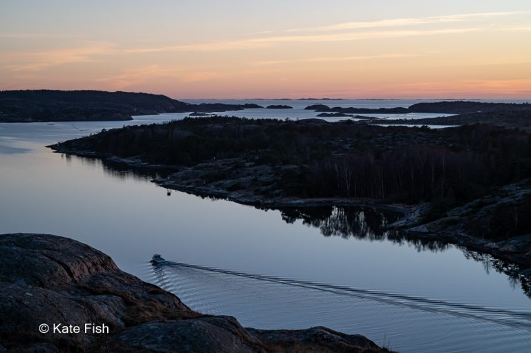 Ausfahrendes Boot bei Sonnenuntergang aus dem Hafen von Grebbestad an der Westküste Schwedens alles nur als Silhouette im Gegenlicht