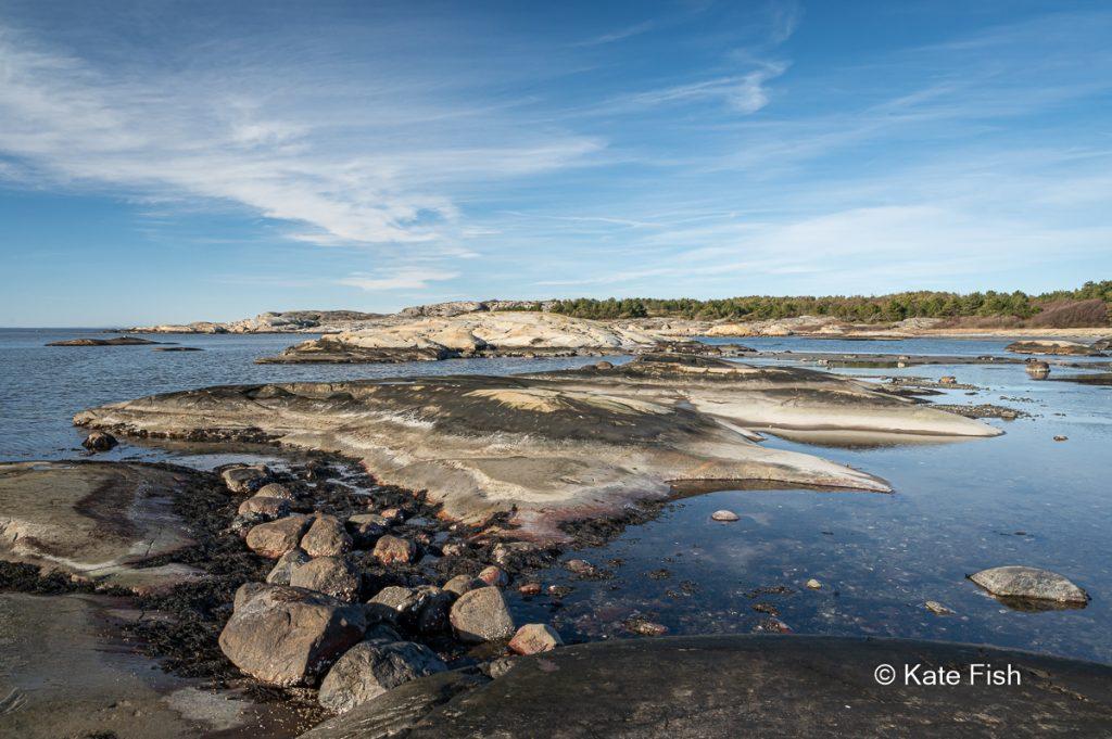 Steinbuckel aus dem flachen Wasser ragend am Strand von Nord Koster im Kosterhavet Nationalpark an der Westküste Schwedens